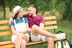 Beautiful couple with suitcase packed for summer journey sitting on bench Royalty Free Stock Images