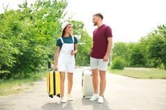Beautiful couple with suitcases packed for summer journey walking outdoors Stock Images