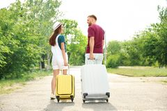 Beautiful young couple with suitcases walking outdoors Stock Images