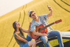 Beautiful young couple taking self portrait from car roof with smart phone against yellow field background. stock photo