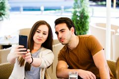 Beautiful young couple taking selfie while sitting at cafe`s garden stock image