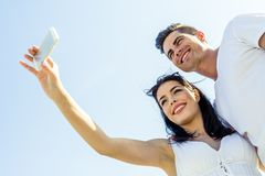 Beautiful  young couple taking a selfie on a summer day. Beautiful  young couple taking a self portrait on a summer day Stock Image