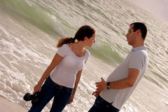 Beautiful young couple talking in front of the oce. Young couple at the beach in the gulf of mexico having a serious discussion, she is looking away with waves Stock Photography
