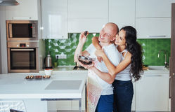 Beautiful young couple is talking, looking at camera and smiling while cooking in kitchen. Stock Photo