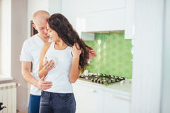 Beautiful young couple is talking, looking at camera and smiling while cooking in kitchen. Stock Photos