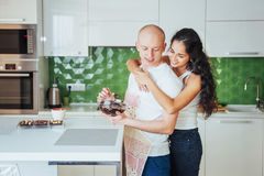 Beautiful young couple is talking, looking at camera and smiling while cooking in kitchen. Royalty Free Stock Image