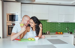 Beautiful young couple is talking, looking at camera and smiling while cooking in kitchen. Royalty Free Stock Photos