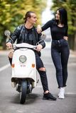 Beautiful young couple talking and smiling while sitting on scooter outdoors Stock Images