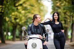 Beautiful young couple talking and smiling while sitting on scooter outdoors Stock Photography
