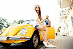 Beautiful young couple talking and smiling while standing near their new convertible Stock Photo