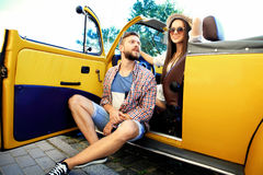 Beautiful young couple talking and smiling while standing near their new convertible Stock Images