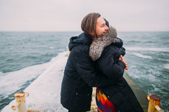 Beautiful young couple tenderly hugging on stoned pier during rainy autumn day. Winter sea background Stock Images