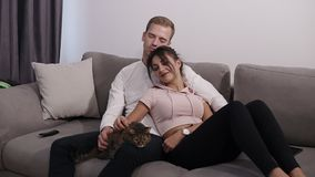 Beautiful young couple with their cat on their living room couch. Young man and woman caress their pet.  stock video