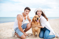 Beautiful young couple with their dog on the beach. Portrait of beautiful young couple with their dog on the beach Stock Photos