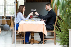 Beautiful young couple toasting wine glasses in the restaurant. Royalty Free Stock Image