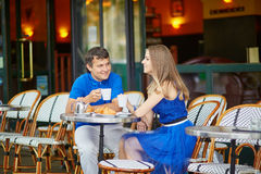 Beautiful young couple of tourists in Parisian street cafe Stock Images