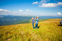 Finding the right path. The beautiful young couple traveling in the mountains and tries to find out their location Royalty Free Stock Images
