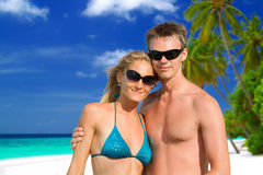 Beautiful young couple on the tropical beach Stock Photos