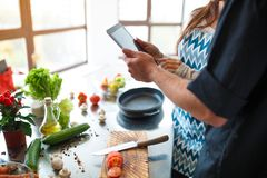 Beautiful young couple uses a digital tablet while cooking food in the kitchen at home stock photography