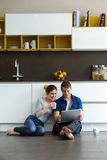 Beautiful young couple using they digital tablet in the kitchen. Stock Photography