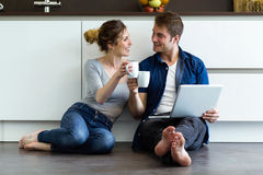 Beautiful young couple using they digital tablet in the kitchen. Stock Photo