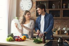 Beautiful young couple reading recipe on tablet. Beautiful young couple is using a digital tablet and reading the recipe on culinary website while cooking in Stock Photo