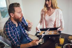 Beautiful young couple is using a digital tablet and smiling while cooking in kitchen stock image