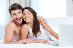 Beautiful young couple using laptop and looking at camera Stock Photo