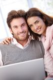 Beautiful young couple using laptop smiling. Beautiful young couple using laptop at home, smiling at camera Royalty Free Stock Image