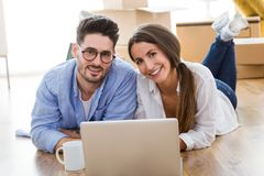 Beautiful young couple using laptop in their new home. Stock Images