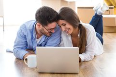 Beautiful young couple using laptop in their new home. Stock Photo