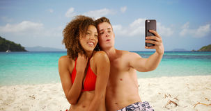 Beautiful young couple using smartphone to take selfie on beach. stock photo