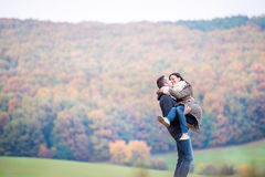 Beautiful young couple on a walk. Colorful autumn nature. Beautiful young couple on a walk, men carrying women in his arms. Colorful autumn nature Royalty Free Stock Image