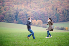 Beautiful young couple on a walk. Colorful autumn nature. Royalty Free Stock Photos