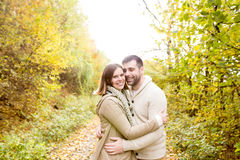 Beautiful young couple on a walk in colorful autumn nature. Beautiful young couple in warm clothes on a walk in forest, hugging. Colorful autumn nature Stock Photography