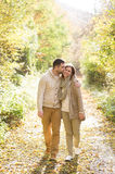 Beautiful young couple on a walk in colorful autumn nature. Beautiful young couple in warm clothes on a walk in forest, hugging and kissing. Colorful autumn Royalty Free Stock Photo