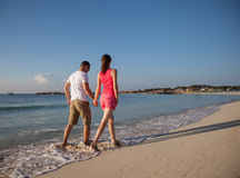 Beautiful young couple walking along the seashore Stock Image
