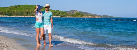 Beautiful young couple walking at beach during. Young couple walking at beach during tropical vacation in Sardinia Stock Photos