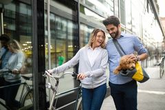 Beautiful couple walking dogs and bicycles outdoors in city stock photography