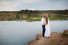 Beautiful young couple walking near the lake on the wedding day Stock Images