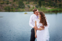 Beautiful young couple walking near the lake on the wedding day Stock Photos