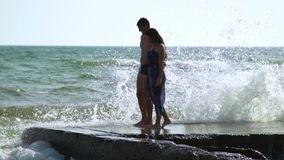 Beautiful young couple walking near the sea in a storm. The waves break about the pier. A guy in swimming trunks, a girl in a swim. Suit and a pareo. Slow motion stock video footage