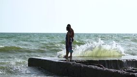 Beautiful young couple walking near the sea in a storm. The waves break about the pier. A guy in swimming trunks, a girl in a swim. Suit and a pareo. Slow motion stock video