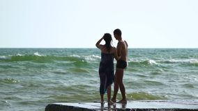 Beautiful young couple walking near the sea in a storm. The waves break about the pier. A guy in swimming trunks, a girl in a swim. Suit and a pareo. Slow motion stock footage