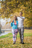 Beautiful young couple walking together in the park. Autumn environment Royalty Free Stock Photo