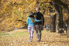 Beautiful young couple walking together in the park. Back view. Autumn environment Royalty Free Stock Image