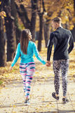 Beautiful young couple walking together in the park. Back view. Beautiful young couple walking together in the park. Autumn environment Royalty Free Stock Photography