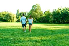 Beautiful young couple walking together in the park stock photography