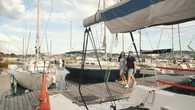 Beautiful young couple walks on a yacht port. Beautiful young couple on yacht stock video footage
