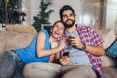 Young couple watching TV in living room stock photo